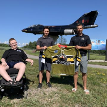 Voodoos northern scout Dillon Anderson (far left), new Voodoos recruit Ben White (middle) and Voodoos assistant coach Josh Dale (right) stand in front of a CF-101 Voodoos Jet at CFB North Bay.